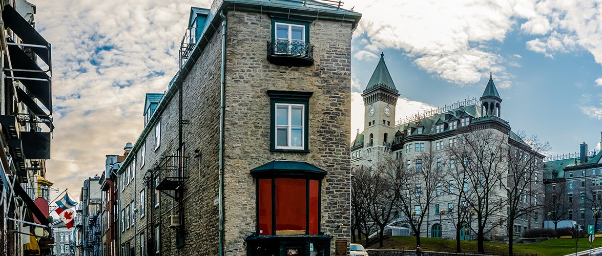 The streets of old Quebec City with thin intertwining stone town housing and a clock tower building.