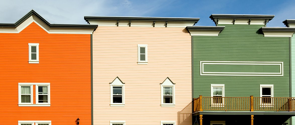 Large colourful town homes painted bright orange, light salmon and olive green.