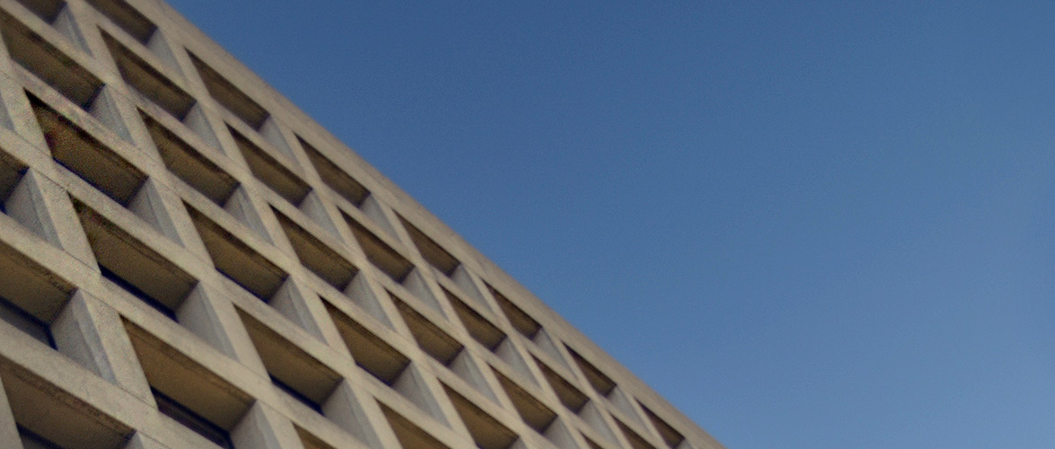 Beige concrete building with square windows under a blue sky.