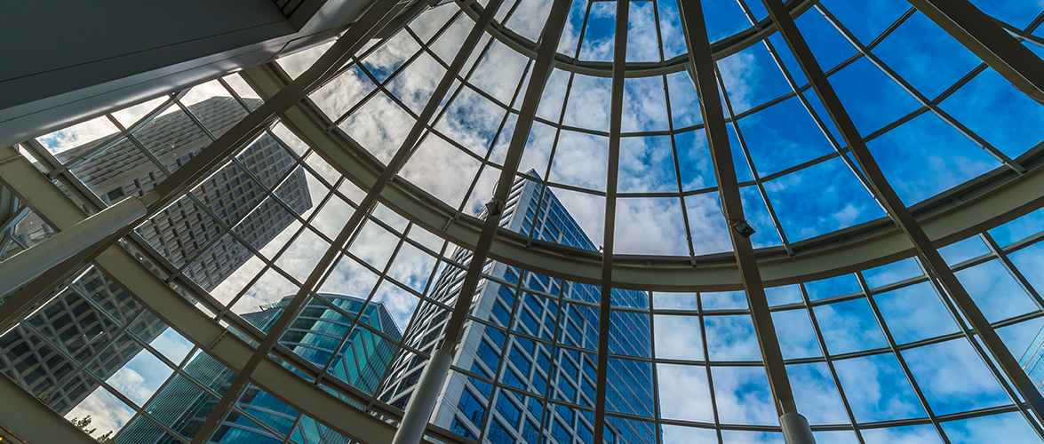 A view of large glass office buildings from inside a glass dome roof.