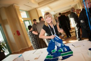 Women holding a blue Reebok jersey at the 2015 Habitat Auction in Kelowna, BC